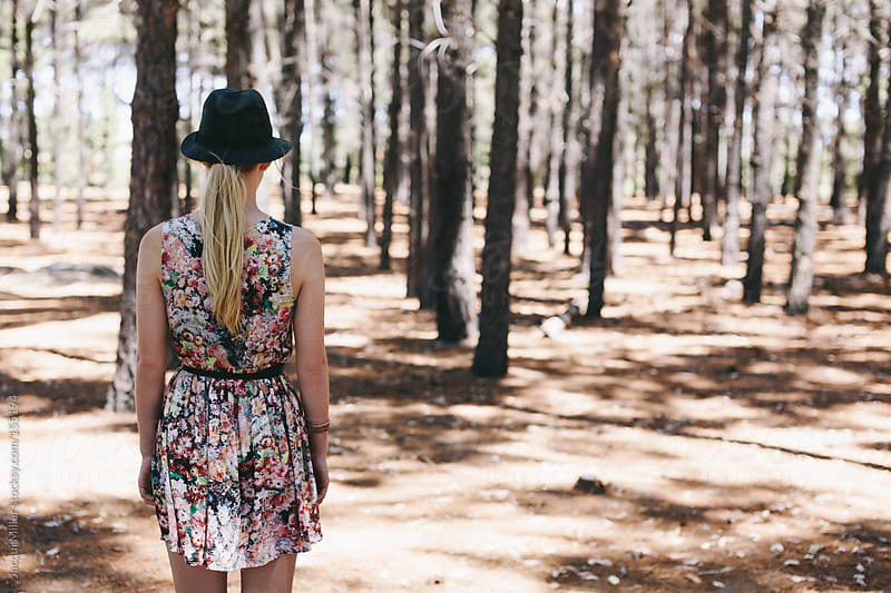 Girl standing in a forest with her back to the camera.  by Jacqui Miller for Stocksy United