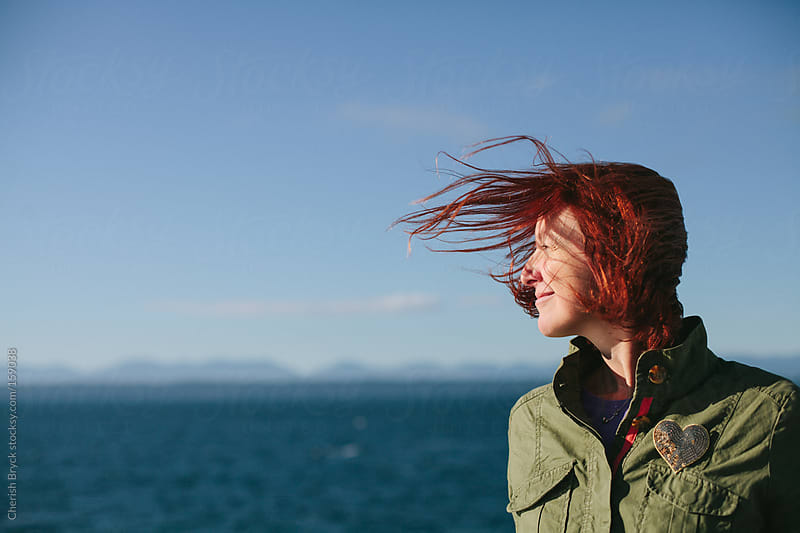 Wind swept hair on the ocean. by Cherish Bryck for Stocksy United