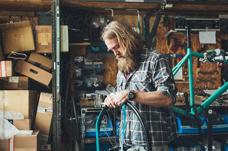 Blond Male Hipster Mechanic Assembling Wheel of Fixed Gear Bike in Bright Workshop by VISUALSPECTRUM for Stocksy United