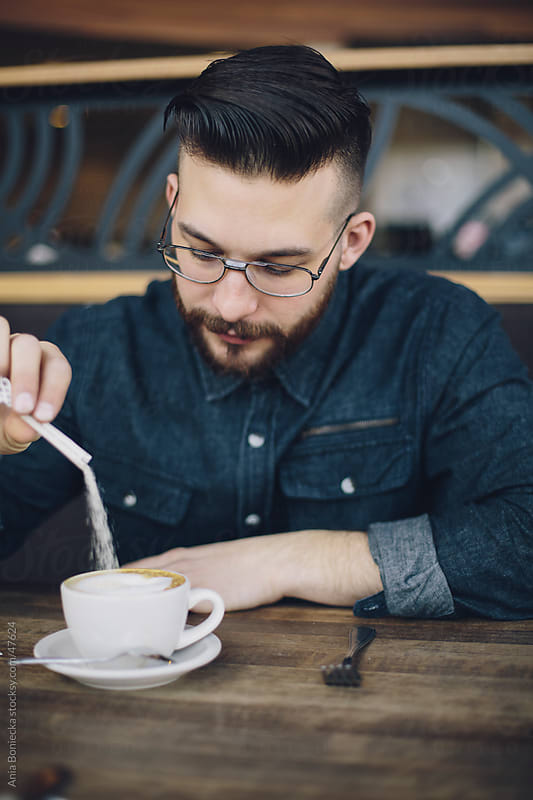 Man pouring sugar into coffee by Ania Boniecka for Stocksy United