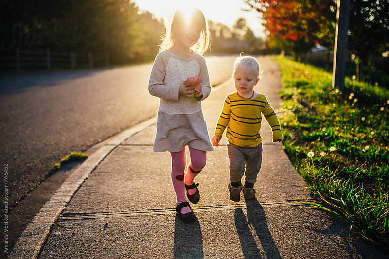 Young Girl and Her Toddler Brother Walk on the Sidewalk in the evening light by Amanda Voelker for Stocksy United
