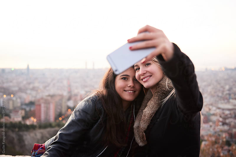 Two young women taking selfie by Guille Faingold for Stocksy United