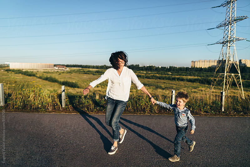 Mother and boy are running by Evgenij Yulkin for Stocksy United