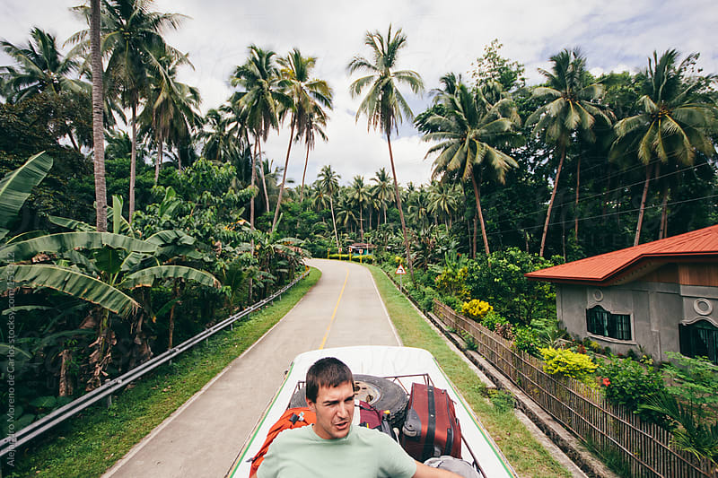 Young man travelling on top of a bus on adventure travel with backpacks and palm trees on background by Alejandro Moreno de Carlos for Stocksy United