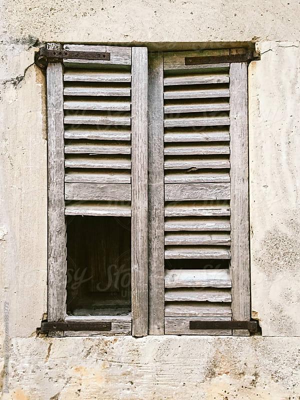 An old broken wooden window shutter by Darren Seamark for Stocksy United