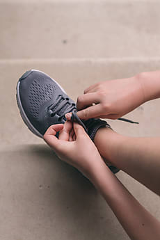 478bd6c0aae4 young woman putting on exercise shoes by Gillian Vann for Stocksy United