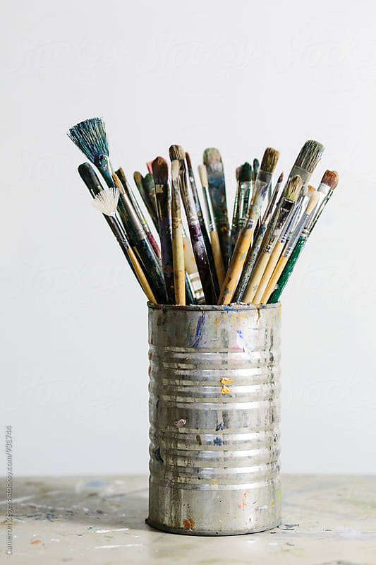 artist brushes in can near blank canvas by Cameron Zegers for Stocksy United