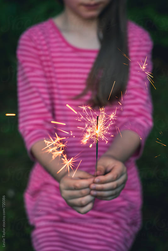 Young Girl In Pink Holding A Sparkler by Leslie Taylor for Stocksy United