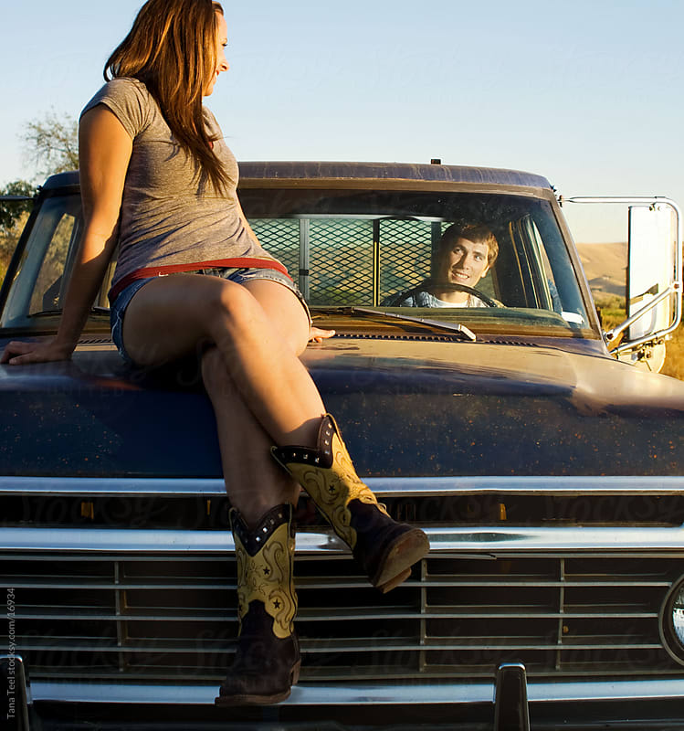 Young woman sitting on hood of old pickup by Tana Teel for Stocksy United