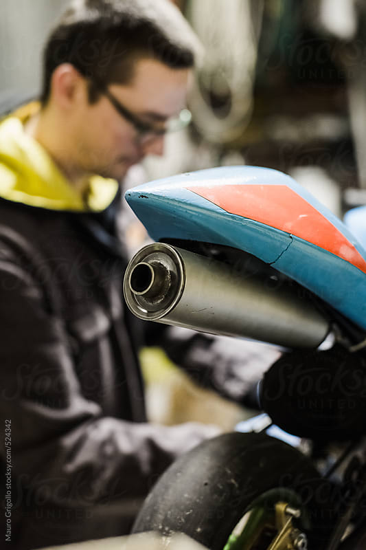 Mechanical operator works on mini motorbike by Mauro Grigollo for Stocksy United