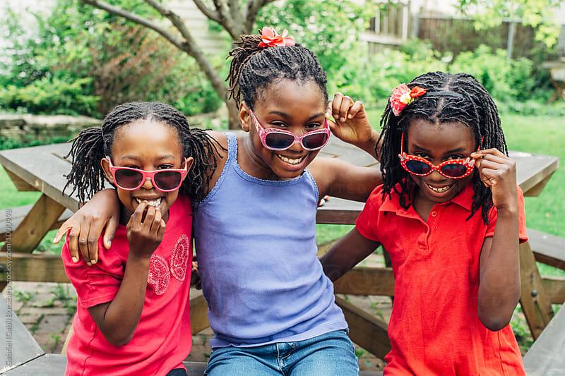 Three black girls on a bench with sunglasses by Gabriel (Gabi) Bucataru for Stocksy United