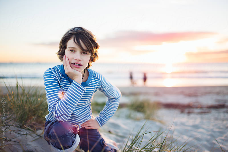 Boy smiling at the beach at sunset by Angela Lumsden for Stocksy United
