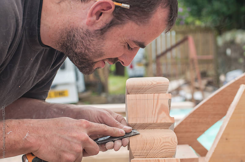 A carpenter carves a piece of wood by Andy Campbell for Stocksy United