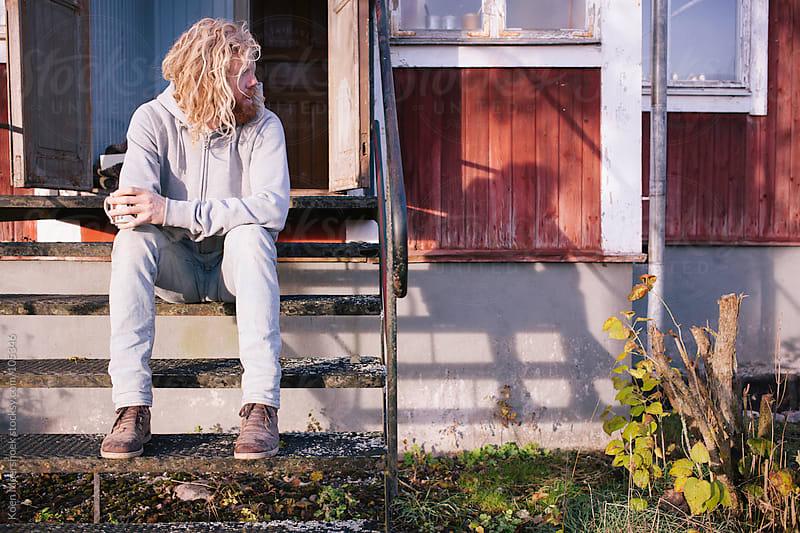 A hairy man having a coffee in the sun. by Koen Meershoek for Stocksy United