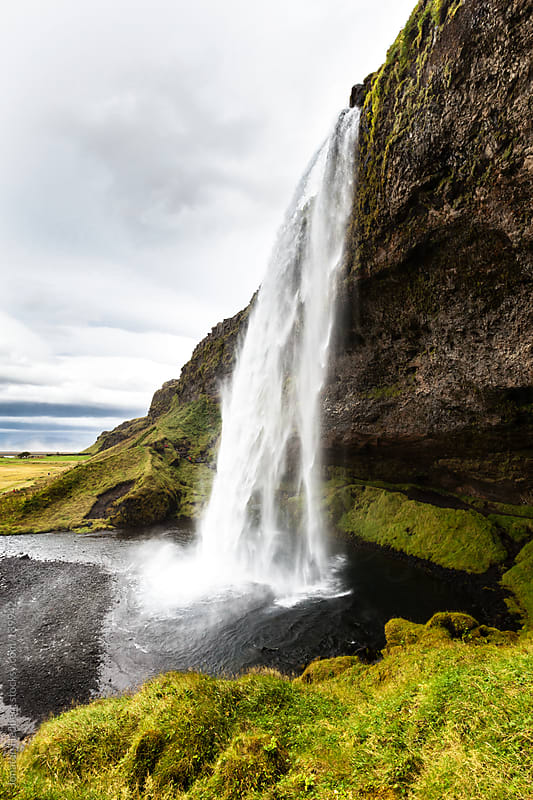 Waterfall in Iceland with heavy rain clouds in the sky by Jonatan Hedberg for Stocksy United