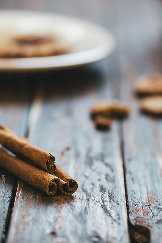 Cinnamon and biscuits on an old wooden table by Aleksandar Novoselski for Stocksy United
