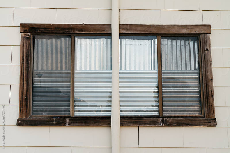 window covered with corrugated metal by Jess Lewis for Stocksy United