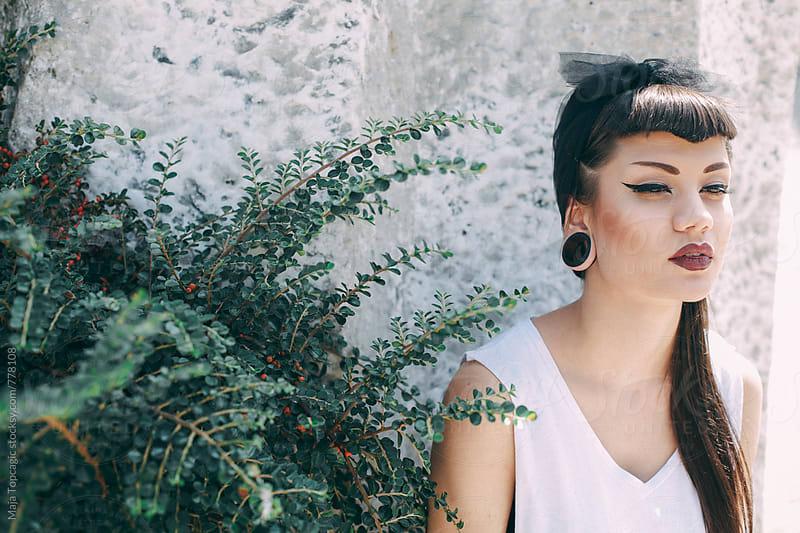 A portrait of a beautiful modern alternative model with black hair  by Maja Topcagic for Stocksy United