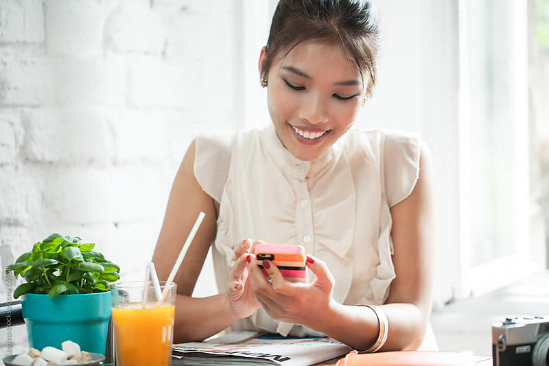 Asian Woman Texting at a Cafe by Lumina for Stocksy United
