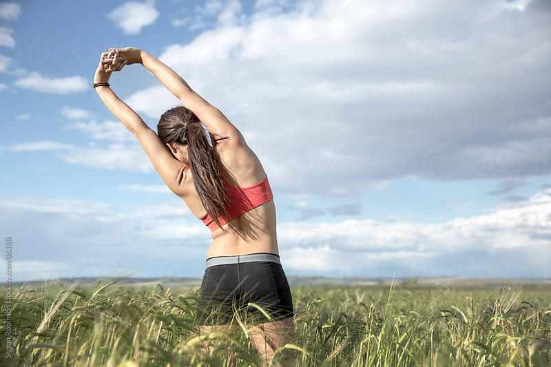a woman in workout clothes stretching in a wheat field by Shaun Robinson for Stocksy United