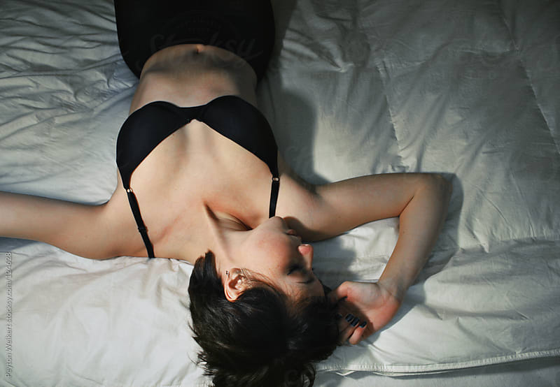 Young woman lying in bed by Peyton Weikert for Stocksy United