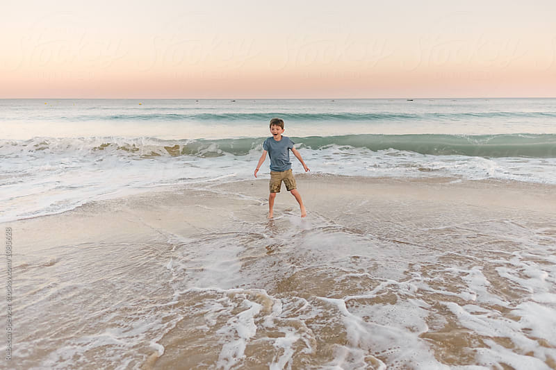 Joyful child playing in the waves by Rebecca Spencer for Stocksy United