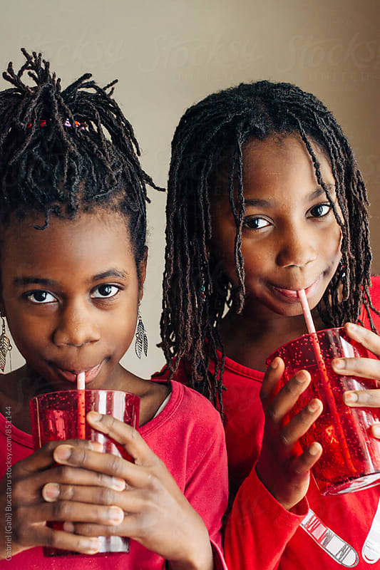 Cute black girls in red outfits sipping juice by Gabriel (Gabi) Bucataru for Stocksy United