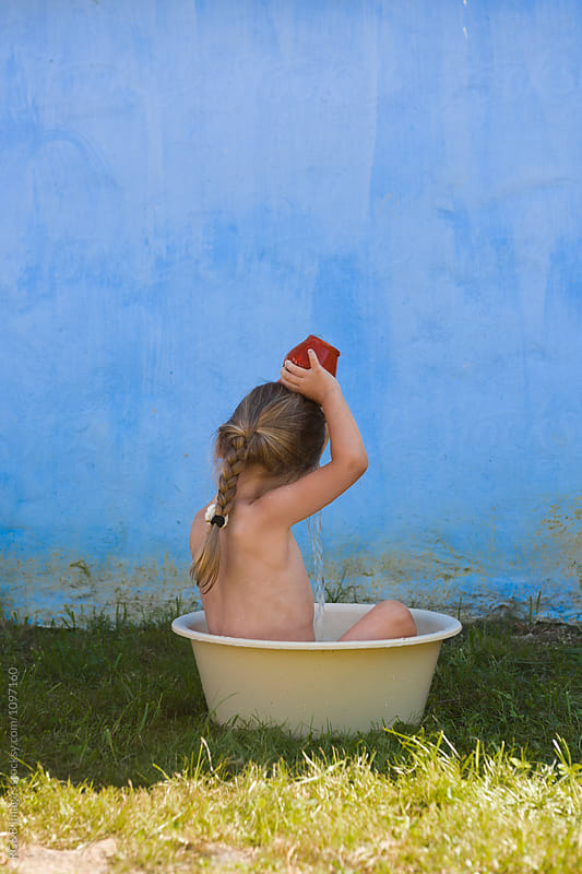 Little girl taking a bath in a plastic basin in the garden by RG&B Images for Stocksy United