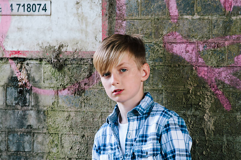 Trendy pre-teen boy standing against a wall. by Helen Rushbrook for Stocksy United