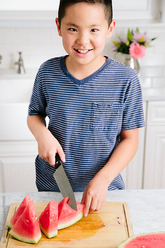 Boy holding knife and cutting watermelon by Curtis Kim for Stocksy United