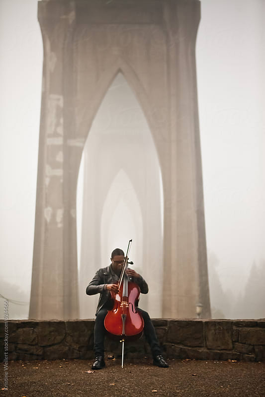 Man playing cello outdoors by Kristine Weilert for Stocksy United