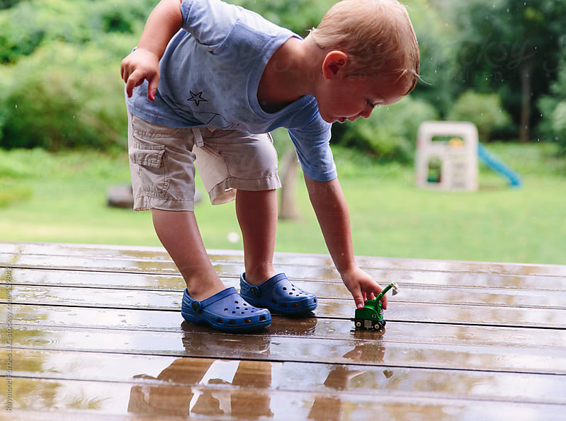 Boy Playing on Deck in Rainstorm by Raymond Forbes LLC for Stocksy United