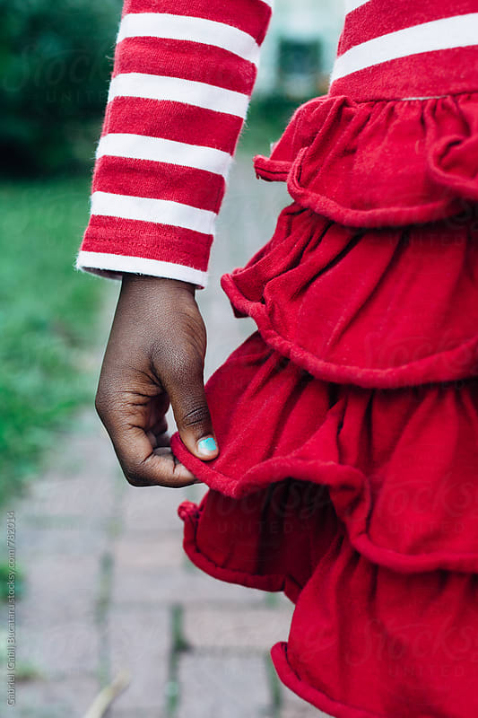 Hand of a black girl holding her red fluffy dress by Gabriel (Gabi) Bucataru for Stocksy United