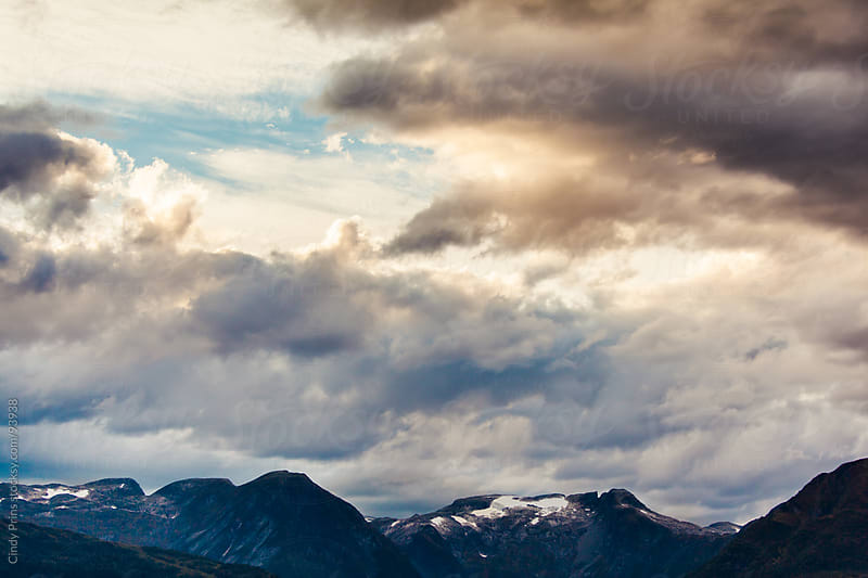 The sun breaking through the clouds over the snowy peaks of Norwegian fjords by Cindy Prins for Stocksy United