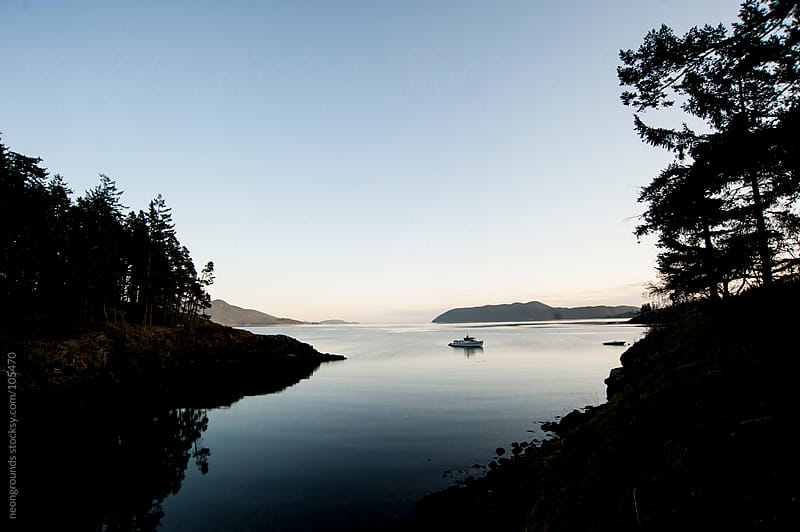 Silhouette of a single boat on the bay at dusk by neongrounds for Stocksy United