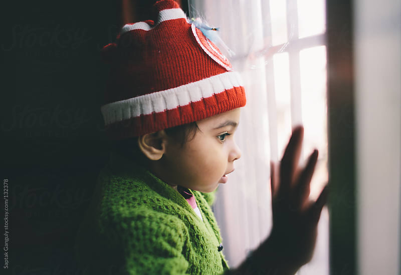Toddler looking out the window by Saptak Ganguly for Stocksy United
