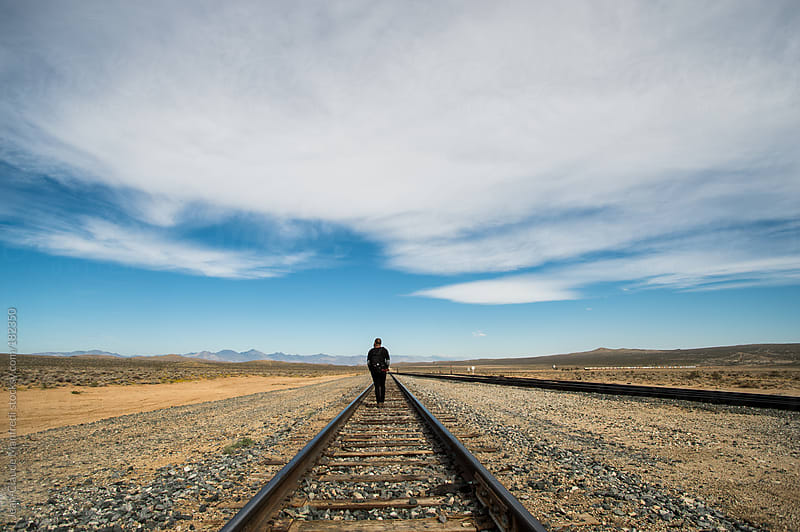 Backpacker walking along a railway in a desert landscape by Jean-Claude Manfredi for Stocksy United