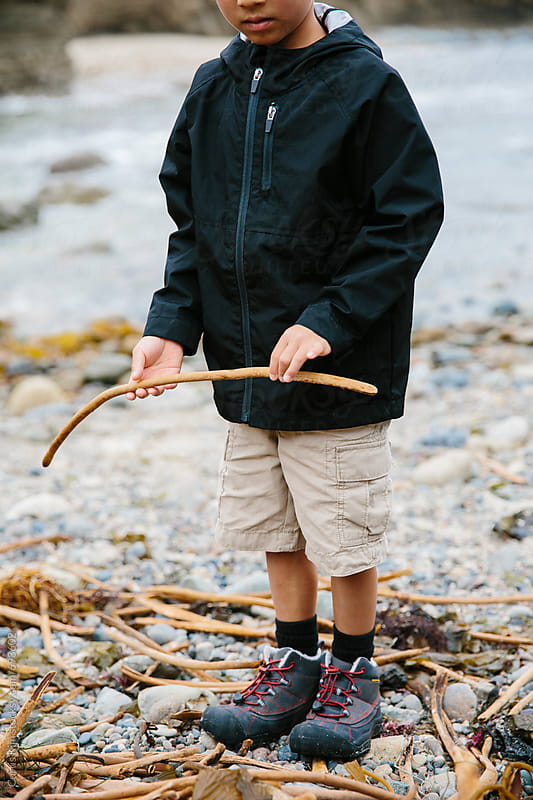 Boy standing on shore during low tide by Curtis Kim for Stocksy United
