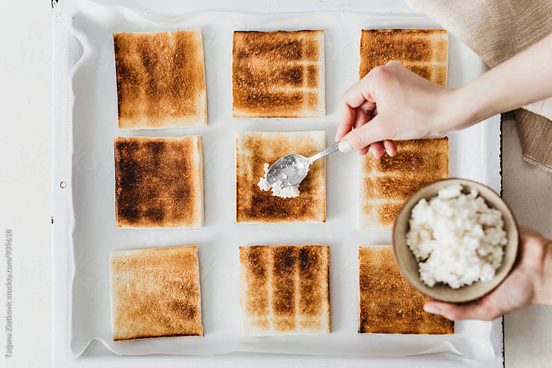 Putting ricotta cheese on toast by Tatjana Ristanic for Stocksy United