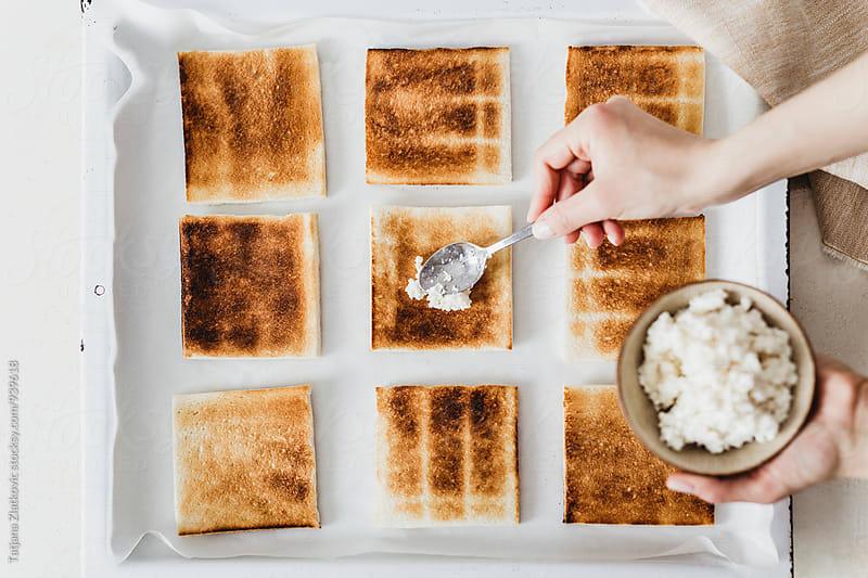 Putting ricotta cheese on toast by Tatjana Zlatkovic for Stocksy United