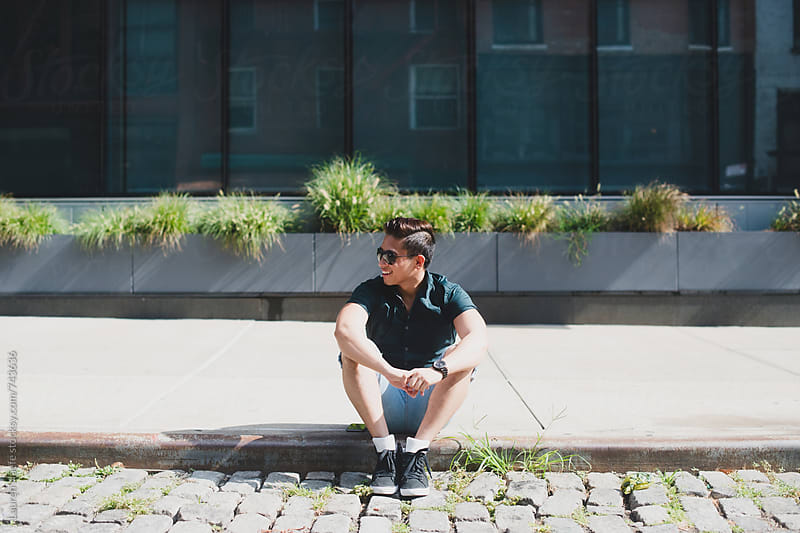 Cute Asian American man sitting on curb on cobblestone in New York City by Lauren Naefe for Stocksy United