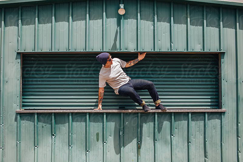 Young  guy jumping off a shed by Gabrielle Lutze for Stocksy United