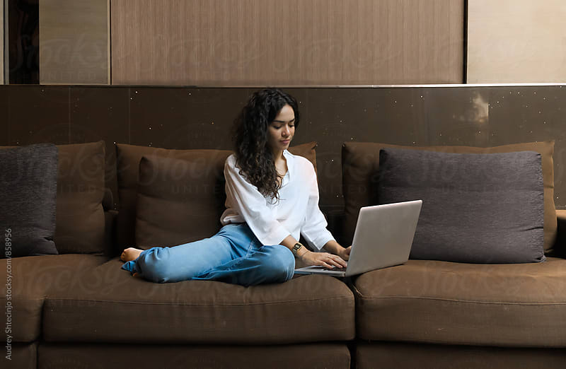 Young student female doing her homework on laptop in home atmosphere. by Marko Milanovic for Stocksy United