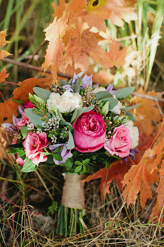 wedding bouquet with colorful flowers on the autumn leaves by Sergey Filimonov for Stocksy United