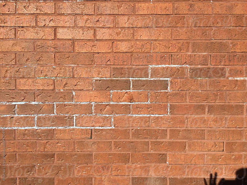 chalk outline on a red brick wall by Amanda Large for Stocksy United