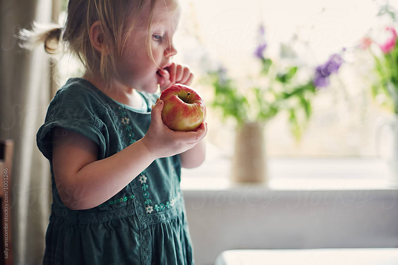 Child eating an apple by sally anscombe for Stocksy United