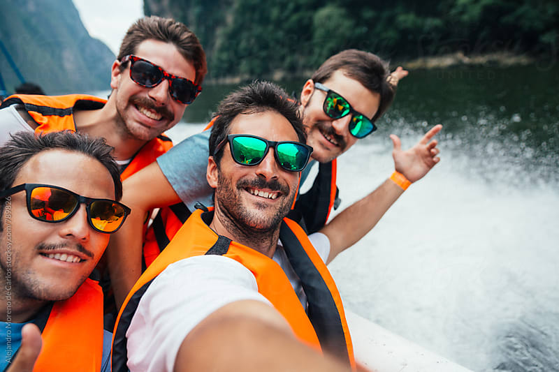 Group of four friends with life jackets and sunglasses having fun on a speedboat on a lake by Alejandro Moreno de Carlos for Stocksy United