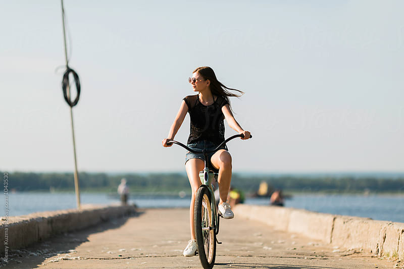 Young Woman Riding a Bike  by Alexey Kuzma for Stocksy United