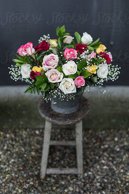 Colourful roses and flowers bouquet in enamel basket on wooden stool