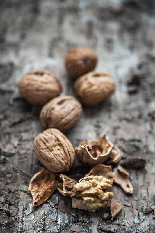 Walnuts on wooden background by Zocky for Stocksy United